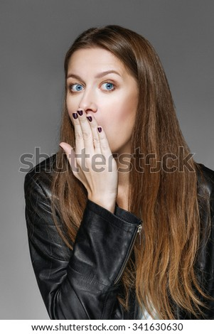 emotional portrait of surprised girl closing her mouth with palm - stock photo