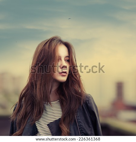 Emotional portrait of the beautiful girl on the roof of the fall - stock photo