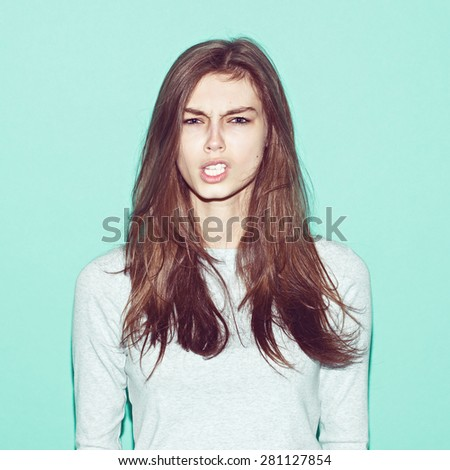 Emotional pretty young hipster girl make funny face on blue background - stock photo