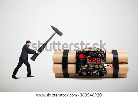emotional screaming businessman holding big hammer and ready to defusing big bomb with timer over light grey background - stock photo
