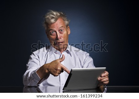 Emotional senior business man with an expressive face pointing to his laptop in horror and disbelief as he sits at a table against a dark studio background with copyspace - stock photo