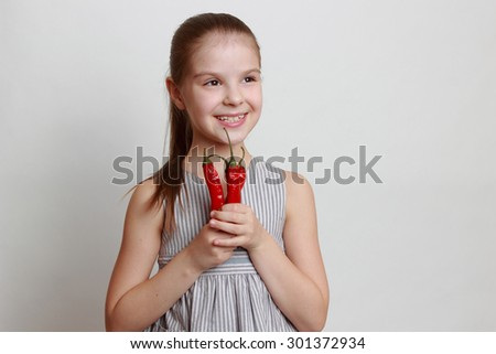 Emotional smiley little girl holding red hot chilli pappers