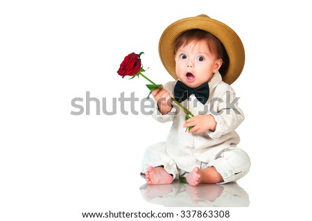 Emotional surprised toddler boy in retro, bow-tie hat and with red rose on white background. - stock photo