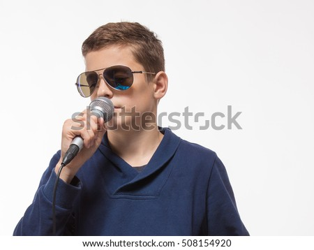 Emotional teenager boy brunette in sunglasses with a microphone on a white background