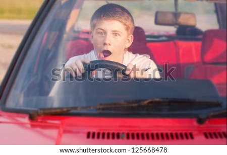 Emotional teenager in car - stock photo