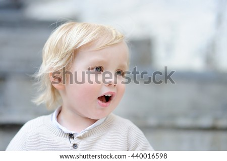 Emotional toddler boy outdoors portrait