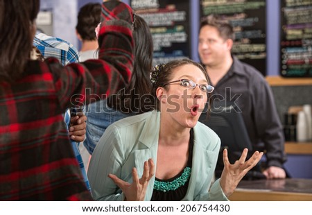 Emotional white female customer in line at coffee house - stock photo