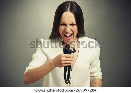emotional woman holding in fist small scared man and yelling at him. photo on dark background - stock photo