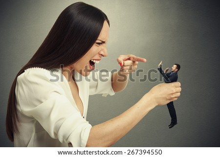 emotional woman holding in hand small scared man, pointing at him and yelling. photo over dark background - stock photo