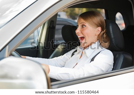 emotional woman in panic is driving the car - stock photo