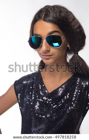 emotional young girl actress brunette wearing sunglasses in black dress on a white background