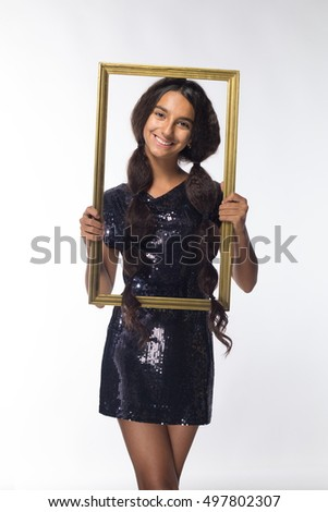 emotional young girl actress brunette with long hair in a black dress with a frame on a white background
