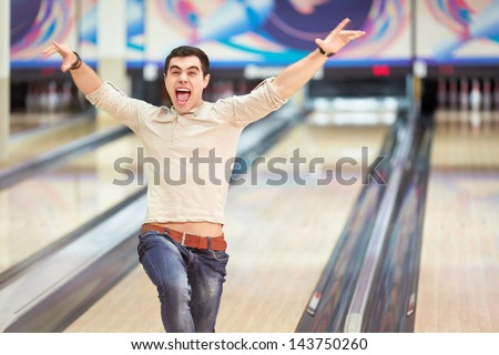 Emotional young man in bowling - stock photo