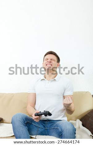 Emotional young man playing video games with joypad or joystick to console or pc. Guy at home in room sitting on bed with thrilled face expression, finally wins his opponent. Photo of winning in game. - stock photo