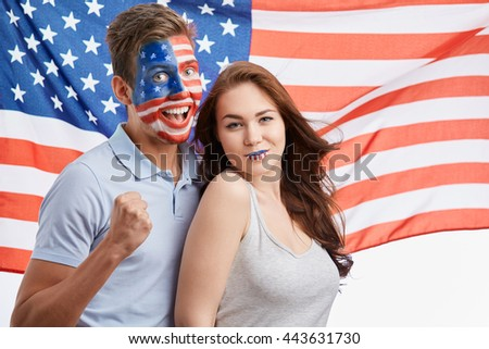 Emotional young patriotic Americans with National make up celebrating Independence Day on 4th of July. American flag on the background, cute heterosexual couple