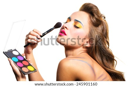 Emotional young woman doing makeup itself. Isolated on white background. - stock photo