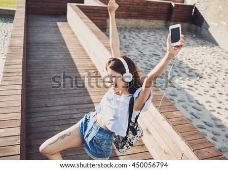 Emotional young woman with headphones listening music outdoors, summer girl portrait - stock photo