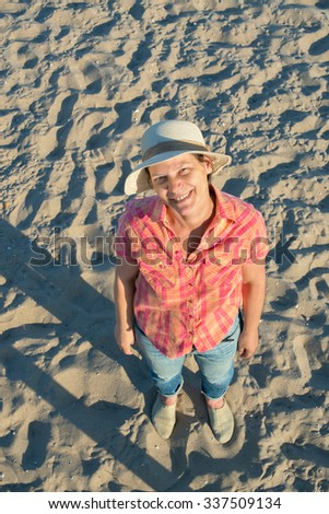 Emotions. Attractive woman with expressive face laughing and looking at camera, having fun in a beach in summer day. Top view. - stock photo
