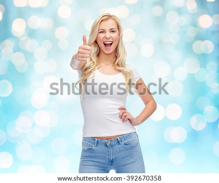 emotions, expressions, advertisement and people concept - happy smiling young woman or teenage girl in white t-shirt showing thumbs up over blue holidays lights background