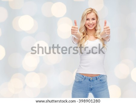 emotions, expressions, advertisement and people concept - happy smiling young woman or teenage girl in white t-shirt showing thumbs up with both hands over holidays lights background - stock photo