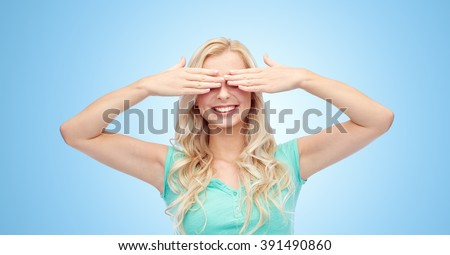 emotions, expressions and people concept - smiling young woman or teenage girl covering her eyes with palms over blue background - stock photo