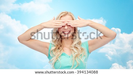 emotions, expressions and people concept - smiling young woman or teenage girl covering her eyes with palms over blue sky and clouds background - stock photo