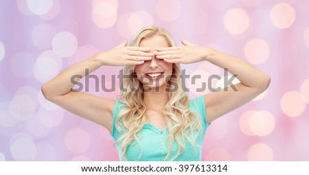 emotions, expressions and people concept - smiling young woman or teenage girl covering her eyes with palms over pink holidays lights background - stock photo