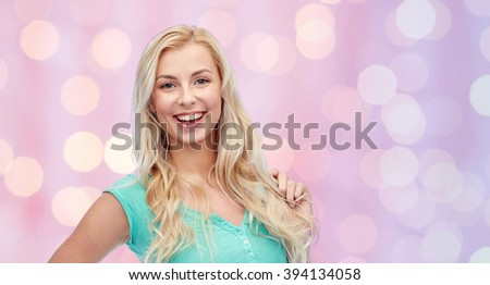 emotions, expressions, hairstyle and people concept - smiling young woman or teenage girl holding her strand of hair over pink holidays lights background - stock photo