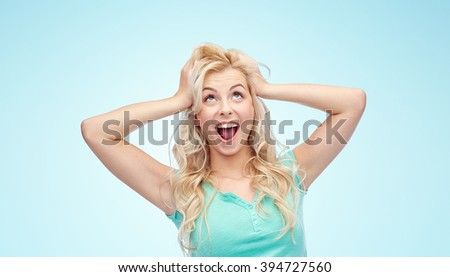 emotions, expressions, hairstyle and people concept - smiling young woman or teenage girl holding to her head or touching hair over blue background - stock photo