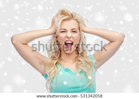 emotions, expressions, hairstyle and people concept - smiling young woman or teenage girl holding to her head or touching hair over snow