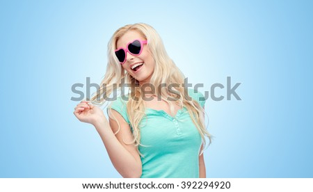 emotions, expressions, summer and people concept - smiling young woman or teenage girl in sunglasses holding her strand of hair over blue background - stock photo