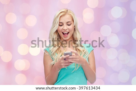 emotions, expressions, technology and people concept - smiling young woman or teenage girl texting on smartphone over pink holidays lights background - stock photo