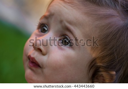 emotions of a little girl, on background of green grass, the evening - stock photo