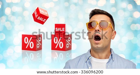 emotions, shopping, sale, discount and people concept - face of scared or surprised middle aged latin man in shirt and sunglasses over blue holidays lights and red percentage signs background - stock photo