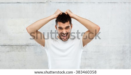 emotions, stress, madness and people concept - crazy shouting man rending ones hair in t-shirt over gray stone wall background - stock photo