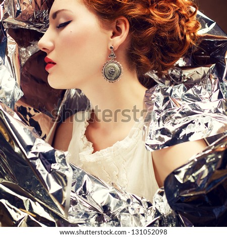 Emotive arty portrait of a fashionable queen-like young woman in white vintage dress posing over wrinkled foil background. Perfect retro hairdo. Close up. Profile. Studio shot - stock photo