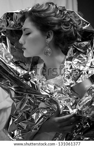 Emotive arty portrait of a fashionable queen-like young woman in white vintage dress posing over wrinkled foil background. Perfect retro hairdo. Close up. Profile. Black & white studio shot