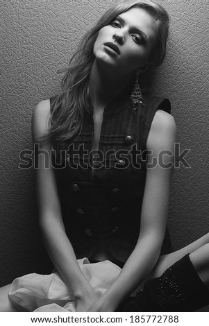 Emotive portrait of a beautiful fashion model posing over gray background. Black and white (monochrome) studio photo