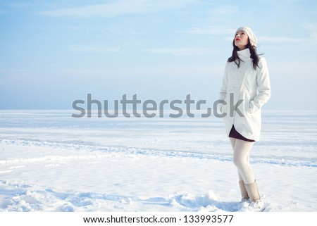 Emotive portrait of a fashionable model in white coat and beret standing at the winter seaside. Sunny weather. French style. Outdoor shot.