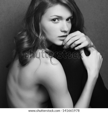 Emotive portrait of a fashionable model with curly hair and natural make-up sitting & posing over gray background. Girl hugs her legs. Perfect skin. Retro style. Black and white studio shot - stock photo
