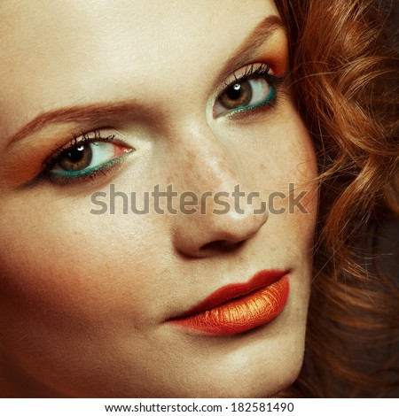 Emotive portrait of a fashionable model with red (ginger) curly hair and arty make-up. Perfect skin with freckles. Retro (disco) style. Close up. Studio shot - stock photo