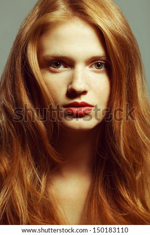 Emotive portrait of a fashionable model with red (ginger) curly hair and natural make-up posing over grey background. Perfect skin with freckles. Retro style. Studio shot  - stock photo