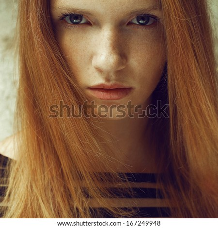 Emotive portrait of a fashionable model with red (ginger) hair and natural make-up. Perfect skin with freckles. Close up. Daylight. Outdoor shot - stock photo