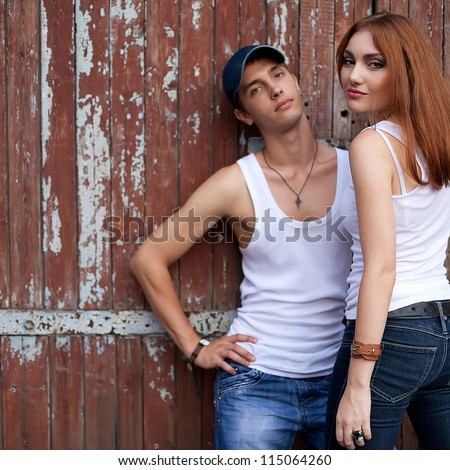 emotive portrait of a stylish couple in jeans standing together near wooden house. outdoor shot