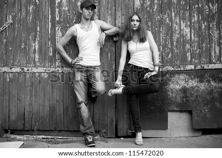 emotive portrait of a stylish couple in jeans standing together near wooden house. outdoor shot - stock photo