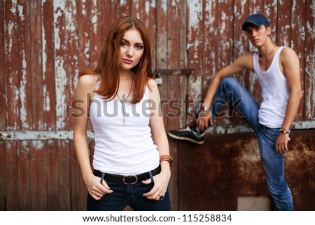 emotive portrait of a stylish smiling couple standing together near wooden house. outdoor shot - stock photo