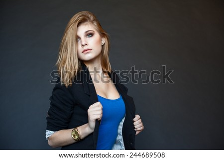 Emotive portrait of a young beautiful girl with curly long hair posing over black background. Perfect skin and hair. Spa salon. Close up. Black and white (monochrome) studio shot - stock photo