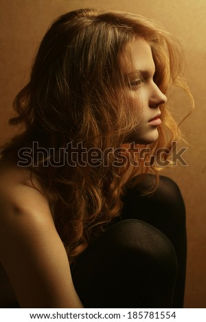 Emotive portrait of a young beautiful girl with red hair in profile hugging her knees and posing over wooden background. Close up. Studio shot
