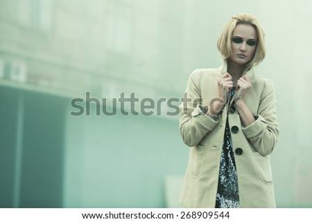 Emotive portrait of beautiful blonde with trendy haircut in beige coat. Perfect make-up. Smoky eyes makeup. Vogue style. Copy-space. Foggy weather. Outdoor shot - stock photo