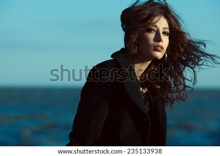 Emotive portrait of beautiful brunette with long curly hair in black coat. Luxurious golden accessories: earrings, necklace. Perfect make-up. Vogue style. Copy-space. Windy weather. Outdoor shot